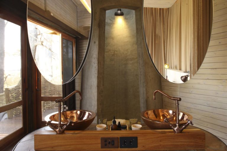 Sandibe's ensuite bathroom have twin copper basins and an open cylindrical shower