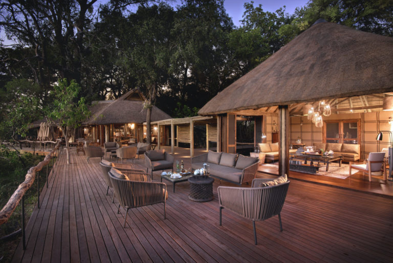 The main teak deck at Nxabega Okavango Tented Camp has expansive seating areas for outdoor dining
