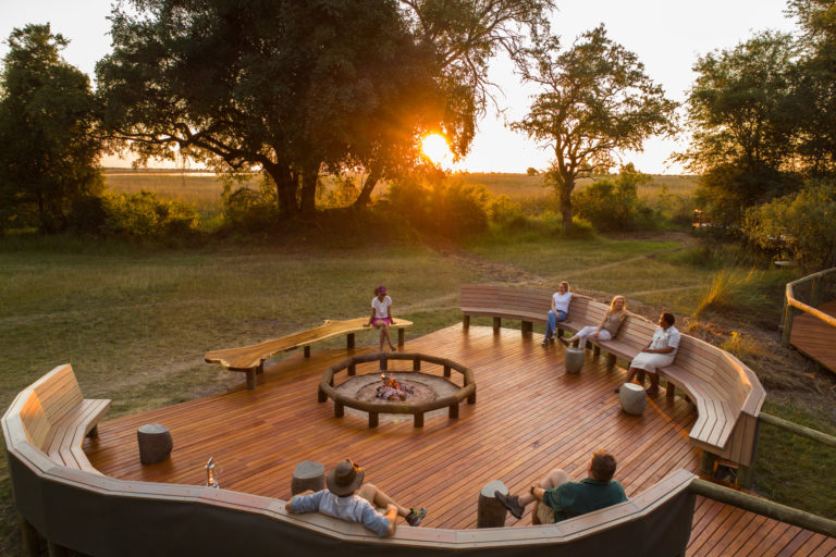 The Camp fire is set up in the centre of the seating area on a wooden deck with gorgeous views of the surroundings at Camp Moremi