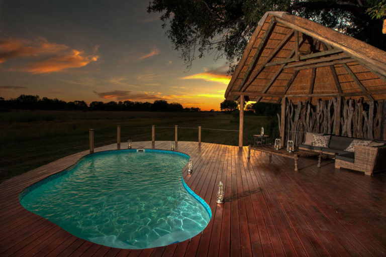 The pristine wooden pool deck at Chitabe Camp lit up by an African sunset