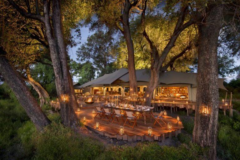 Duba's extended main deck by lantern light under ebony trees.