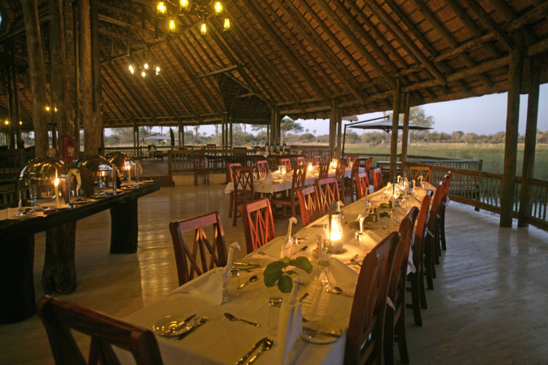 Dining room table set for dinner in spacious main area at Moremi