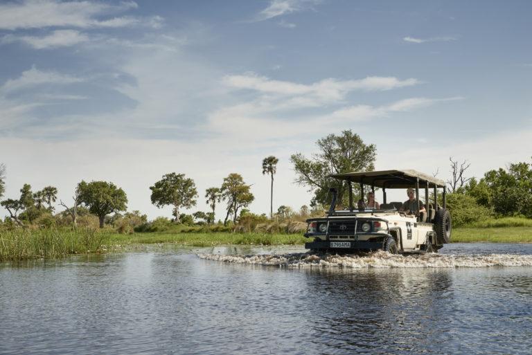 Baine's Camp 4x4 safari vehicle crosses water in the Delta