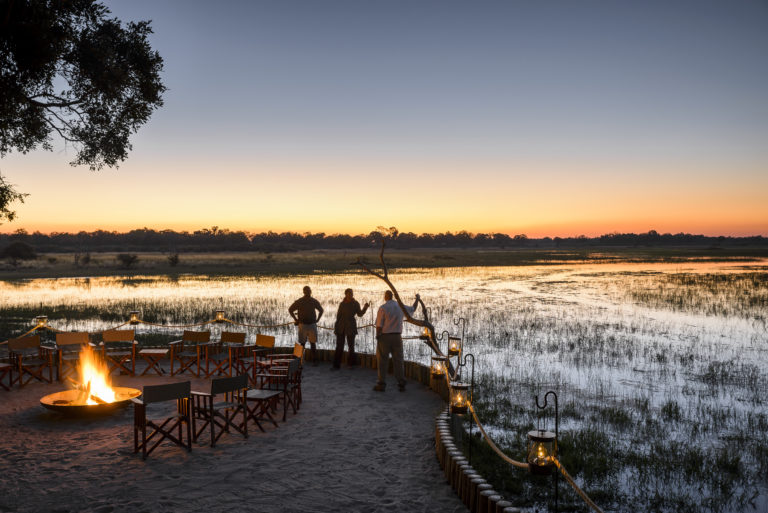 Sundown at Chief's camp accentuated by firepit and Okavango Delta backdrop