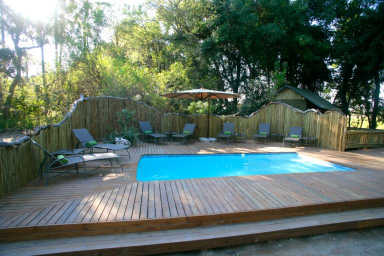 The attractive wooden pool deck at Moremi with shaded sun loungers