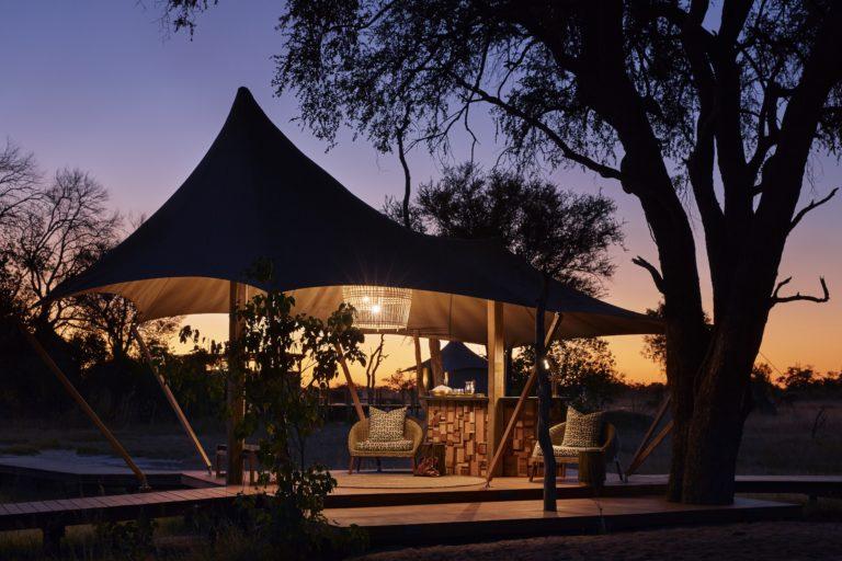 Tuludi Camp by light at night under massive leadwood trees