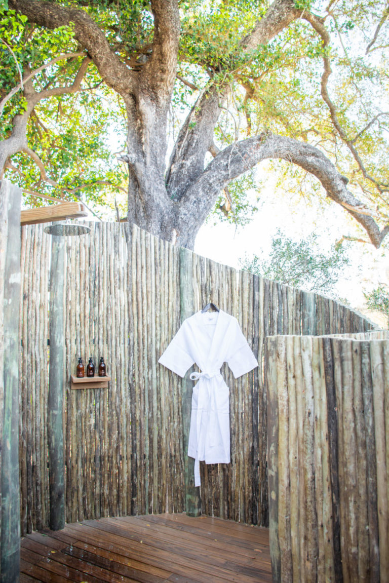 An early morning outdoor shower in natural surroundings at Kwara Camp