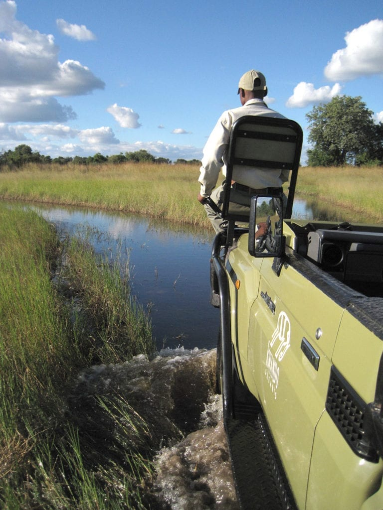 Water crossing on game drive vehicle with tracker at Kwara Camp