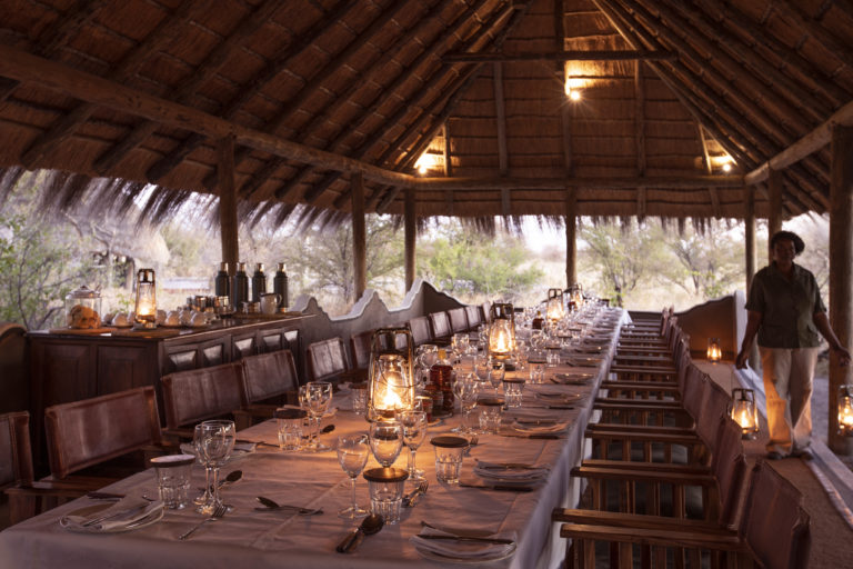 Thatched communal dining room table at Camp Kalahari