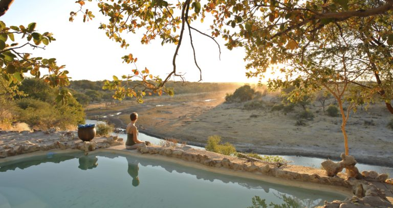 An African sunset peeks over the mountains in full view of Meno a Kwena's swimming pool