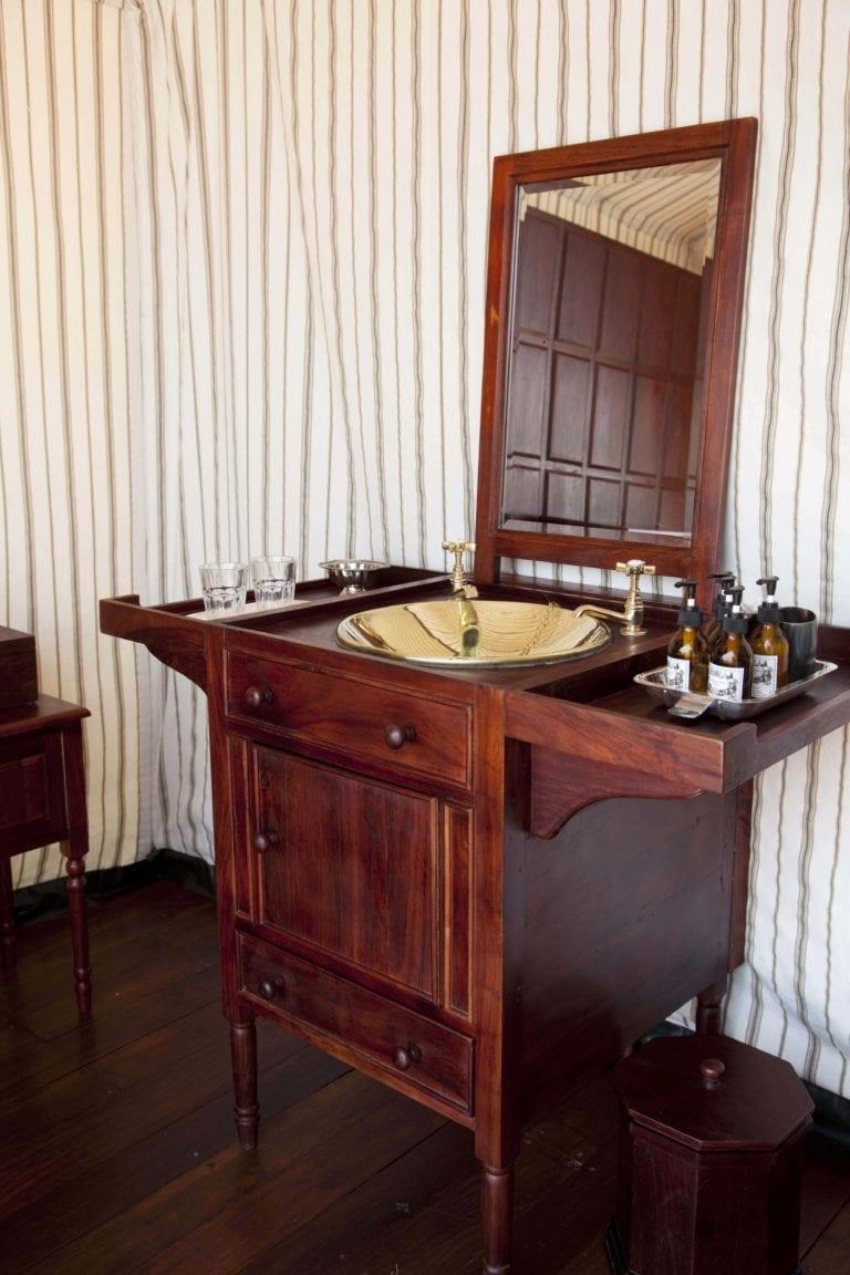 Traditional wooden safari basin and mirror decor at San Camp