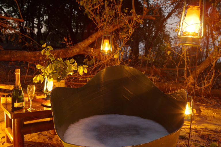 Bubble bath and champagne by lantern light at Footsteps Camp