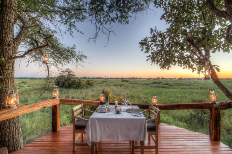 Private dinner for two set up on viewing deck at Camp Okavango