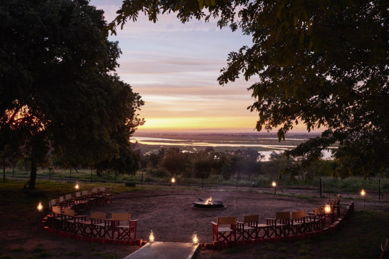 The camp fire and boma at Chobe Chilwero lit up by dawn