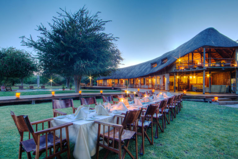 Outdoor dinner set up against backdrop of Leroo La Tau lodge lighting