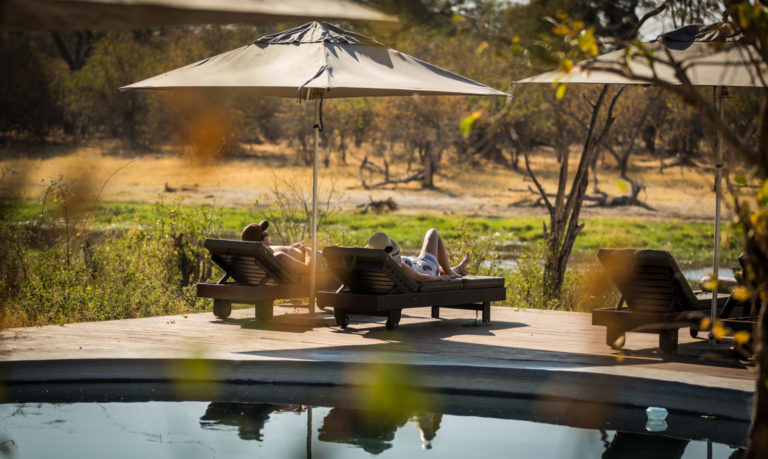 Shaded loungers with wilderness views at Machaba