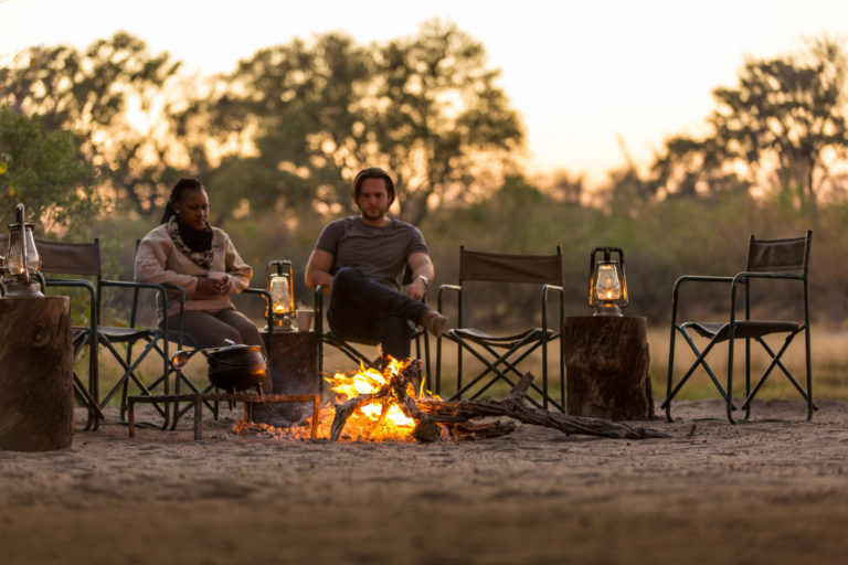 Camp fire drinks and sunset with guests from Machaba Camp