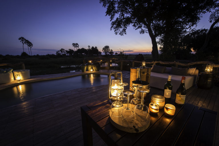Private dinner setup on pool deck at Mombo Camp