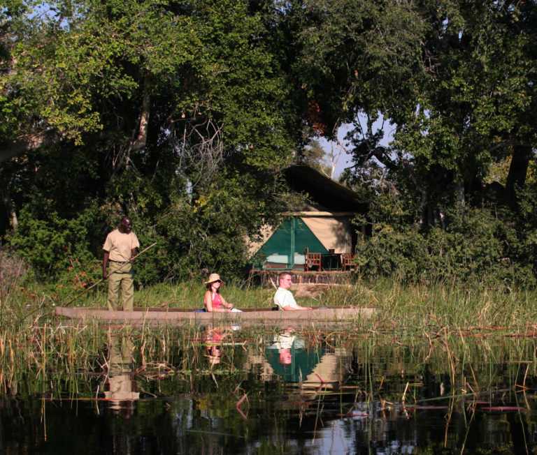 Mokoro glides past front of guest tents in the lagoon at Pom Pom