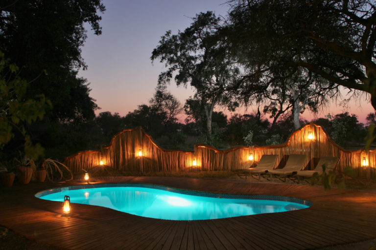 The swimming pool at Pom Pom camp lit up at night