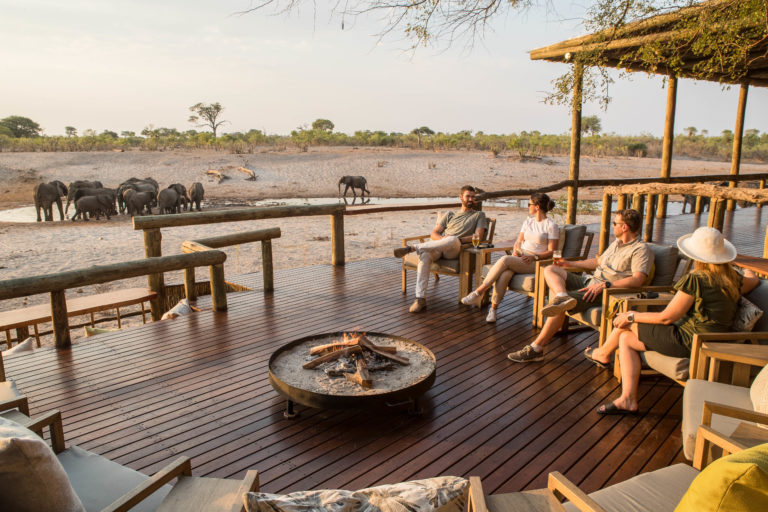 Fire pit and guest seating on wooden deck at Savute Lodge