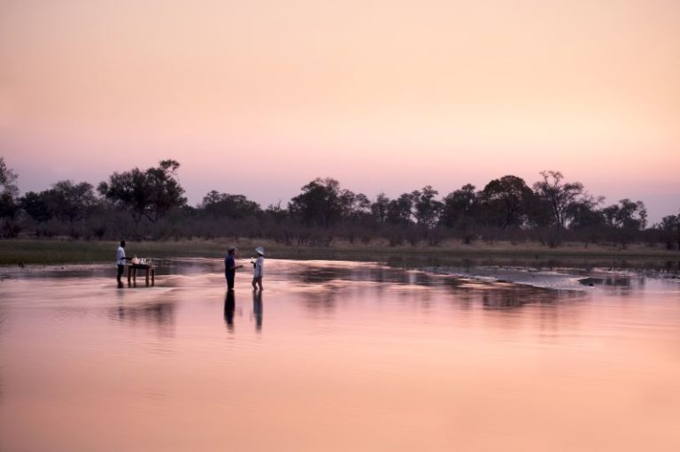 Drinks at sundown with feet in the water at Selinda Explorers Camp