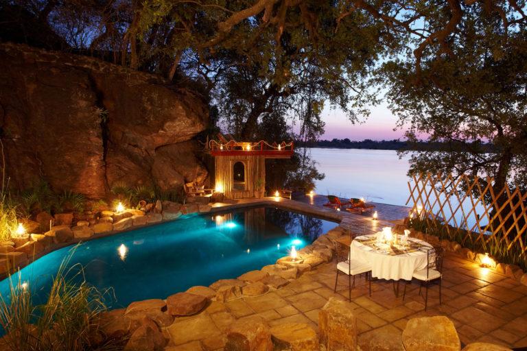 The swimming pool lit at night at the main lodge at Tongabezi