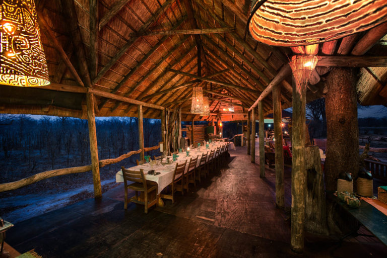 The thatched dining area with dining room table at Hyena Pan Camp