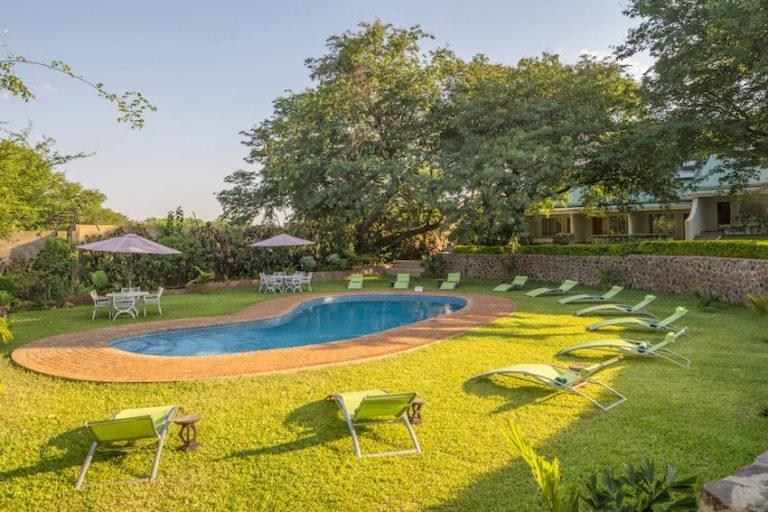 The lush gardens surrounding the pool area at Batonka