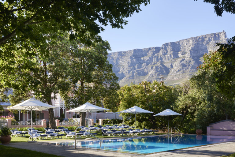 Table Mountain forms the perfect landscaped backdrop to Mount Nelson hotel 's sparkling swimming pool and deck