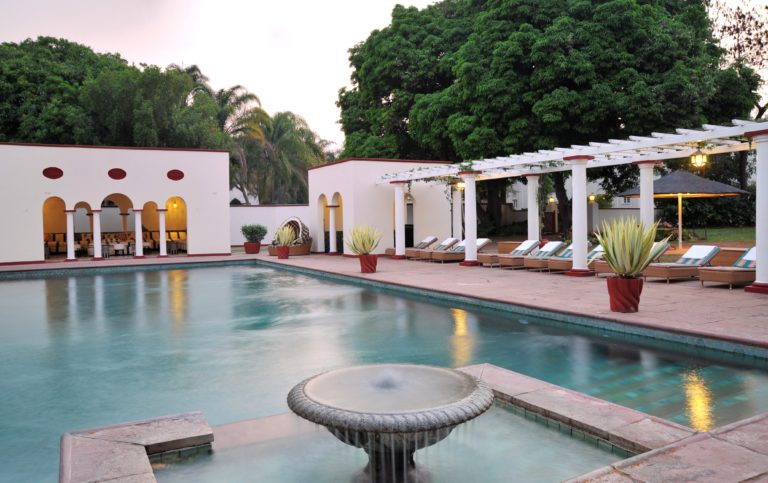 The Edwardian pool at Victoria Falls Hotel is surrounded by lush gardens