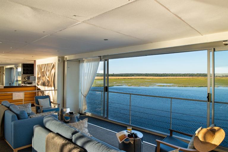 Zambezi Queen lounge area with riverbank viewZambezi Queen lounge area with riverbank view